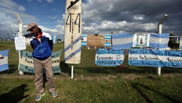 A man stands in front of signs in support of the 44 crew members of the ARA San Juan submarine - Sputnik Mundo