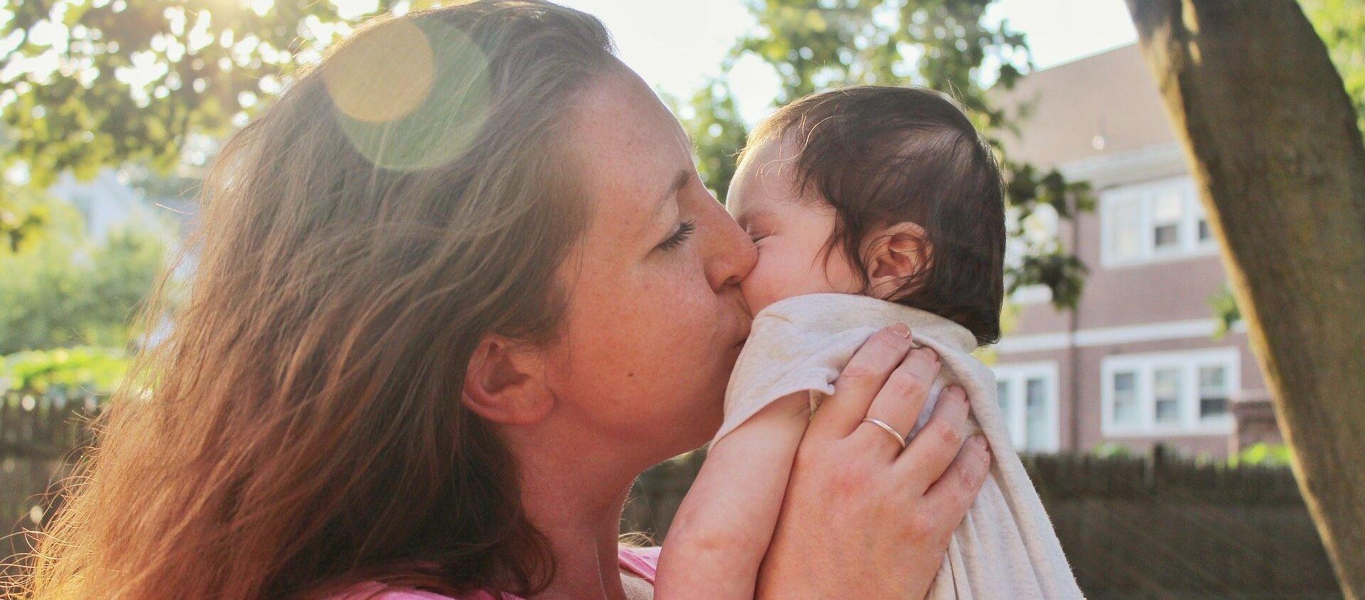 Madre besa a su bebé - Sputnik Mundo, 1920, 13.01.2021