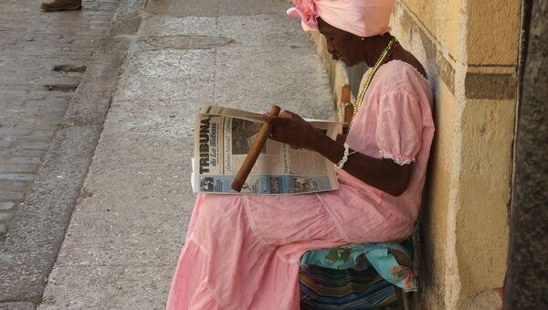 Una mujer cubana lee y fuma un puro en las calles de La Habana (imagen referencial) - Sputnik Mundo