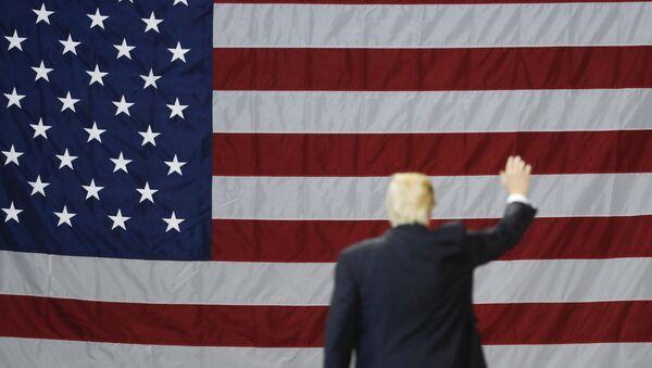 El presidente de EEUU, Donald Trump, con la bandera del país al fondo - Sputnik Mundo