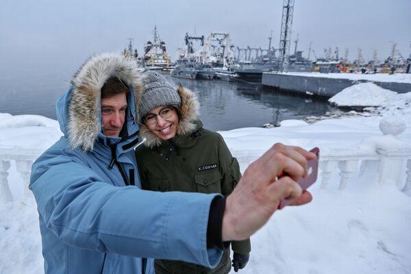 La presentadora de televisión y candidata presidencial por el partido Iniciativa Civil, Ksenia Sobchak, y un miembro de su equipo de campaña, Antón Krasovski, se toman una foto frente a unas naves en la ciudad de Severomorsk, en la región de Múrmansk - Sputnik Mundo