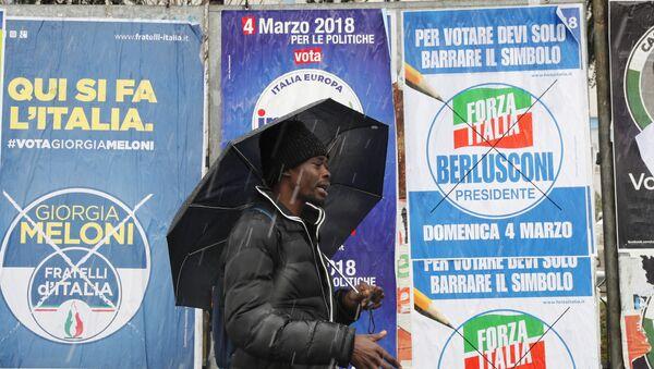 Un inmigrante africano pasa ante carteles electorales para las elecciones generales de Italia - Sputnik Mundo