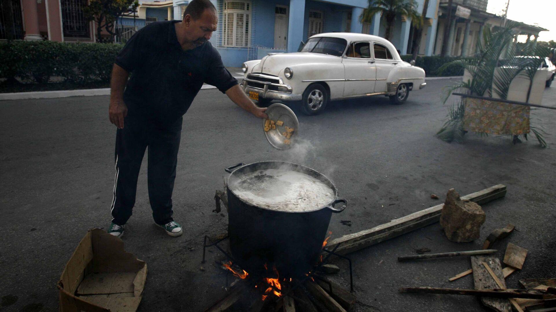 Un hombre prepara caldosa en la calle por el Aniversario de los CDR en Cuba - Sputnik Mundo, 1920, 28.09.2021