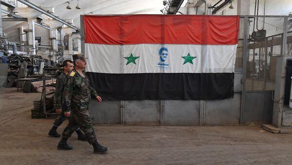 Militares sirios pasan ante la bandera del país (archivo) - Sputnik Mundo