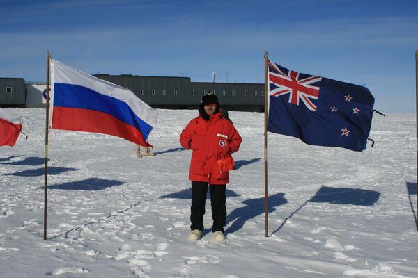Alexandr Nóvikov, investigador de la Universidad Nacional de Investigaciones Nucleares de Rusia (MEPhI), junto a las banderas de Rusia y de Nueva Zelanda, países participantes en los estudios en la Antártida - Sputnik Mundo