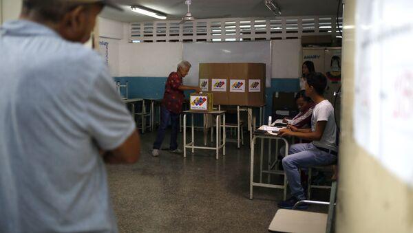 A Venezuelan citizen casts a vote at a polling station during the presidential election in Caracas, Venezuela - Sputnik Mundo