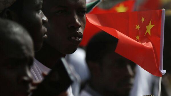 Los senegaleses reciben a la delegación china en el aeropuerto con las banderas de China en las manos - Sputnik Mundo