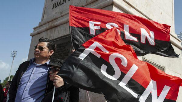Sandinista porta las banderas del FSLN en el 39 Aniversario de la Revolución nicaraguense - Sputnik Mundo