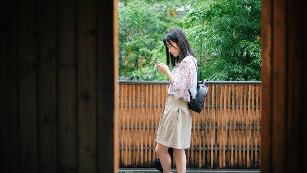 Una joven china con un smartphone - Sputnik Mundo