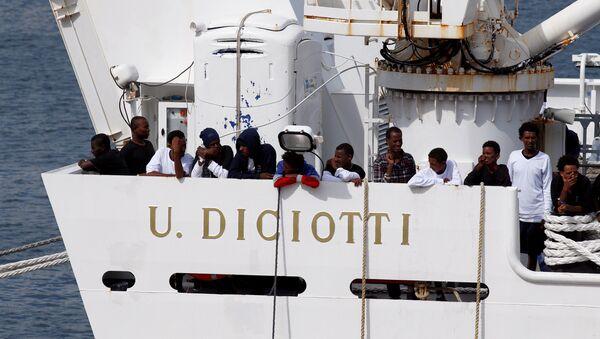 Los migrantes esperan para desembarcar del barco de la guardia costera italiana Diciotti cuando llegan al puerto de Catania, Italia - Sputnik Mundo