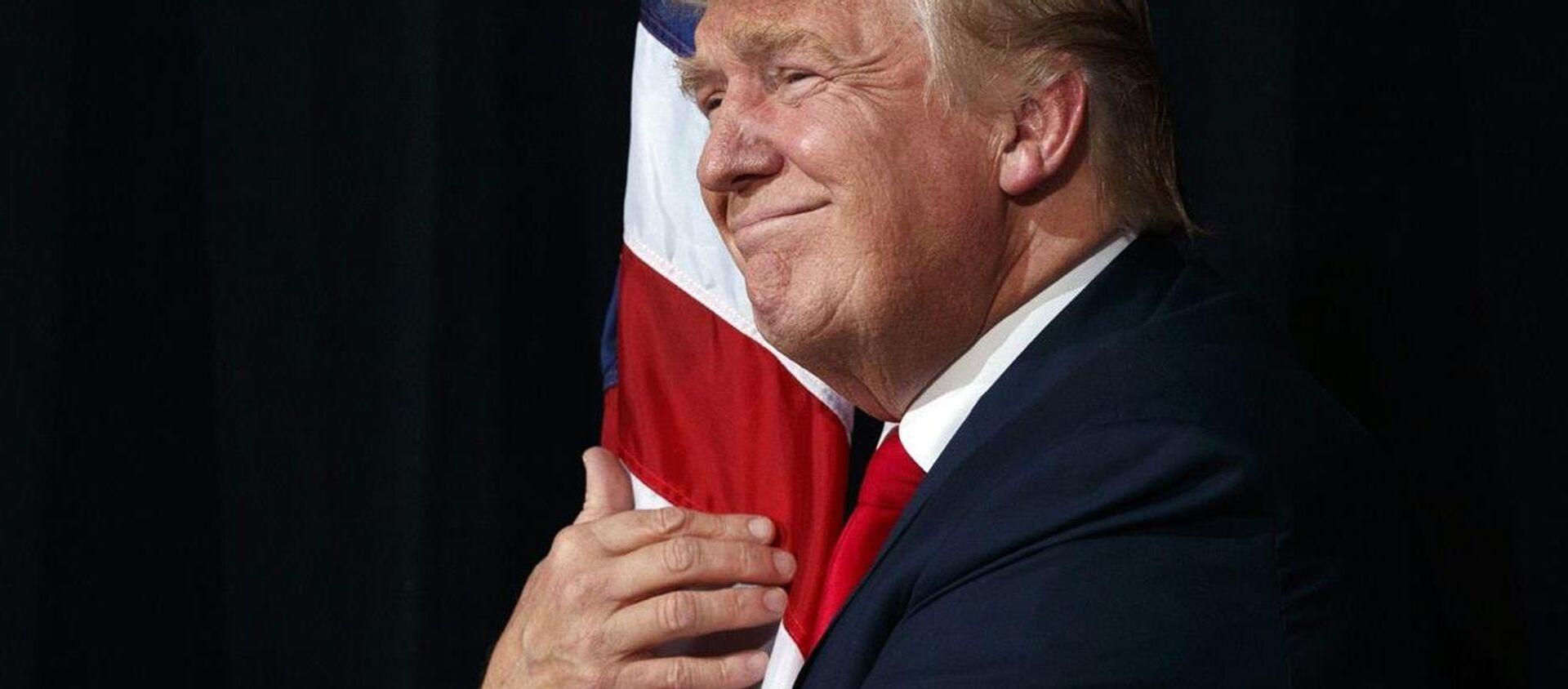 El presidente Donald Trump abraza la bandera de EEUU (archivo) - Sputnik Mundo, 1920, 16.10.2018