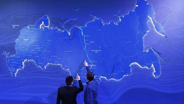 Hombres observando el mapa de Rusia en el Foro Económico de Krasnoyarsk (archivo) - Sputnik Mundo