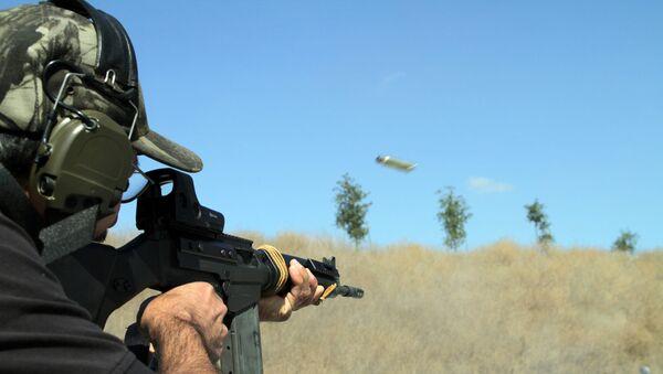 Un hombre lanza disparos con un rifle FAL - Sputnik Mundo