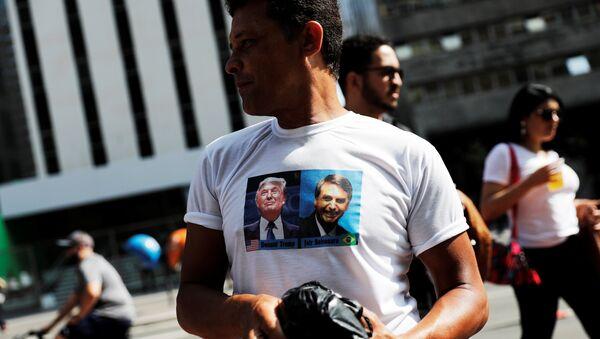 Un hombre con una camiseta con la imagen de Donald Trump y el candidato presidencial brasileño, Jair Bolsonaro. - Sputnik Mundo