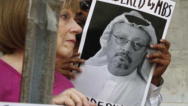 Personas con retratos del periodista saudí Jamal Khashoggi protestan en Washington - Sputnik Mundo