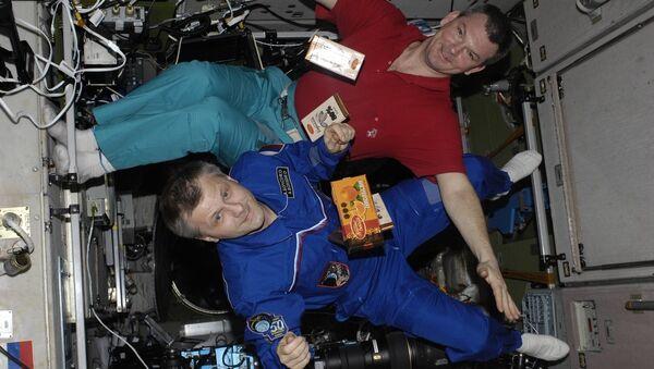 Los cosmonautas con barras de chocolate flotando en EEI (archivo) - Sputnik Mundo