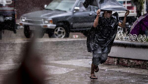 Migrante centroamericano corre de la lluvia y en el parque Miguel Hidalgo de Tapachula - Sputnik Mundo