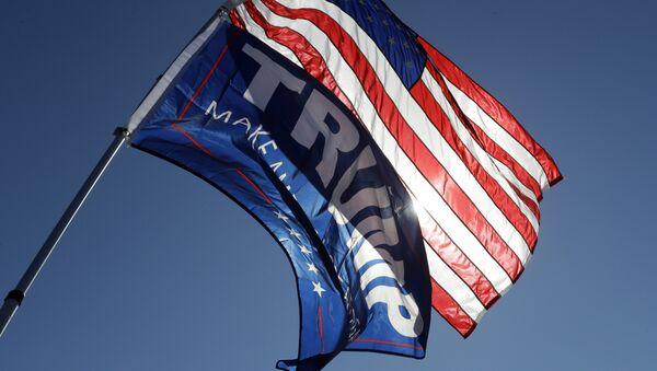 Un partidario del candidato presidencial republicano Donald Trump sostiene la bandera estadounidense y una bandera de campaña de Trump - Sputnik Mundo