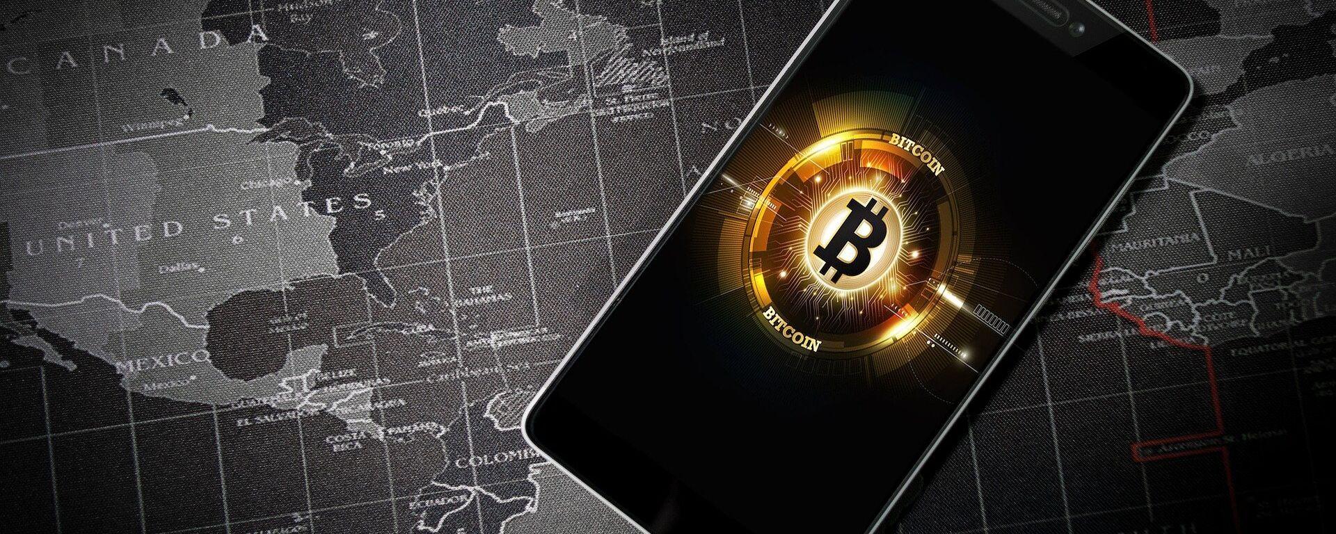 Un móvil con la imagen del logo de bitcoin   - Sputnik Mundo, 1920, 15.01.2021