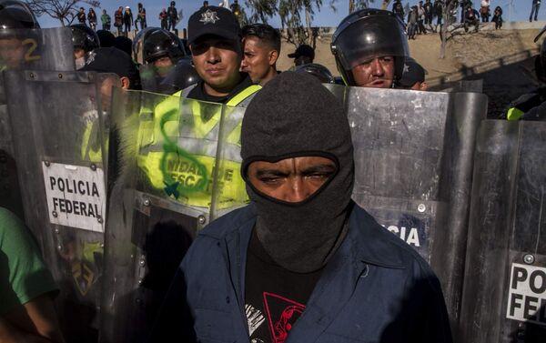 Elementos de la Policía Federal mexicana impiden el paso a un migrante centroamericano - Sputnik Mundo