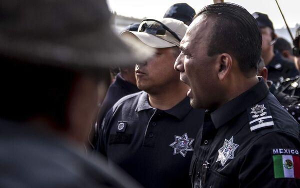 Un policía federal mexicano, Juan Carlos Morán, impide el paso de la manifestación centroamericana a la frontera con EEUU en el paso peatonal el Chaparral - Sputnik Mundo