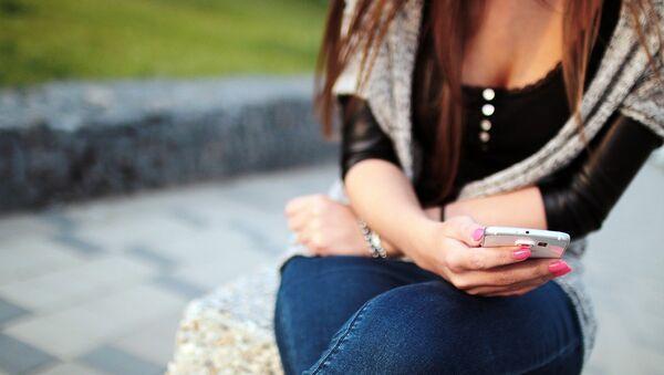 Una chica con su teléfono, referencial - Sputnik Mundo