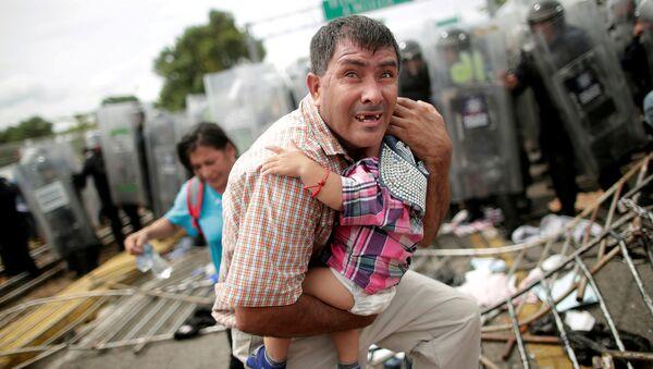 Un migrante trata desesperadamente de proteger a su bebé durante un choque en el cruce de la frontera entre México y Guatemala, el 19 de octubre de 2018 - Sputnik Mundo