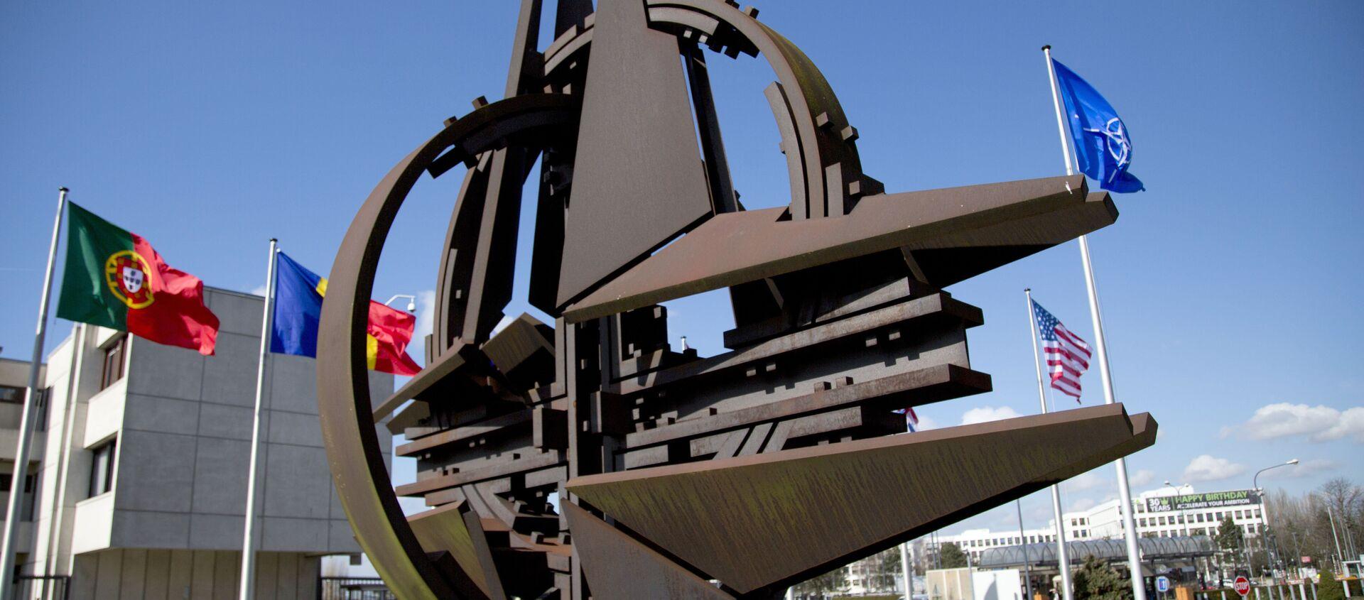 El símbolo de la OTAN y las banderas de Estados que forman parte del bloque militar.  - Sputnik Mundo, 1920, 09.12.2020