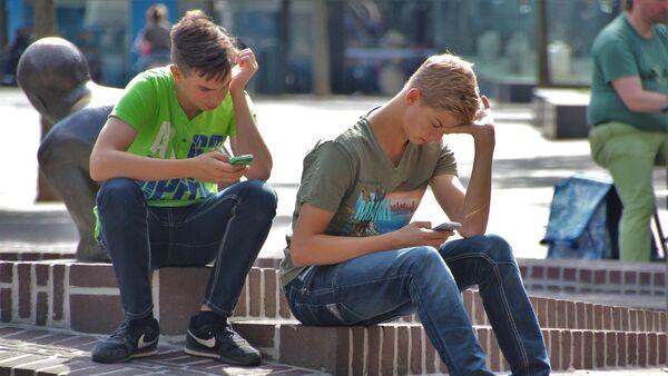 Jóvenes con sus celulares en una plaza - Sputnik Mundo