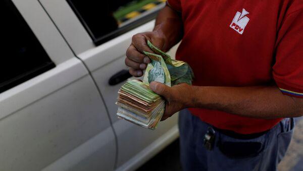 Bolivares venezolanos en las manos de una empleada de PDVSA - Sputnik Mundo
