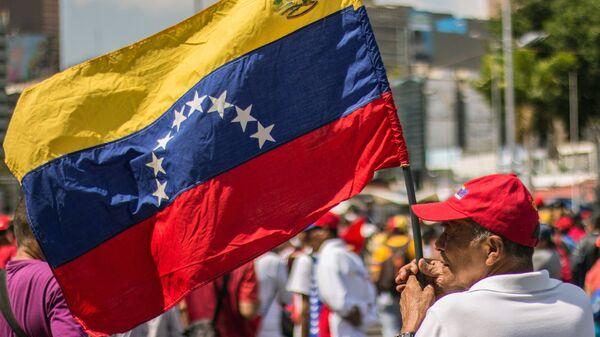 Un hombre con la bandera de Venezuela - Sputnik Mundo