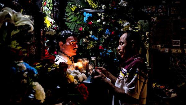 Culiacán, Sinaloa. Hombre reza frente a la imagen de Jesús Malverde en su capilla. - Sputnik Mundo