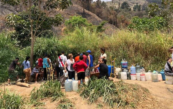 En ocasiones, la gente que espera por llevar agua a sus casas intercambia opiniones sobre la coyuntura venezolana - Sputnik Mundo