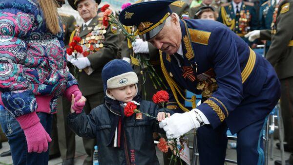 Un niño regala claveles rojos a un veterano durante las celebraciones del Día de la Victoria de 2017, en el Parque de la Victoria en Moscú - Sputnik Mundo