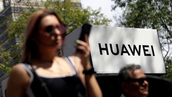 Personas pasando cerca de un cartel de Huawei en Ciudad de México - Sputnik Mundo