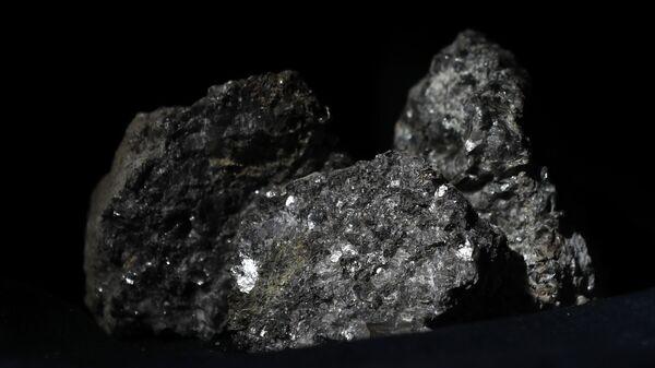 Partículas de litio brillan en la superficie de un mineral  - Sputnik Mundo