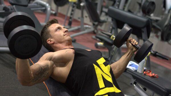 Un hombre con pesas en un gimnasio - Sputnik Mundo