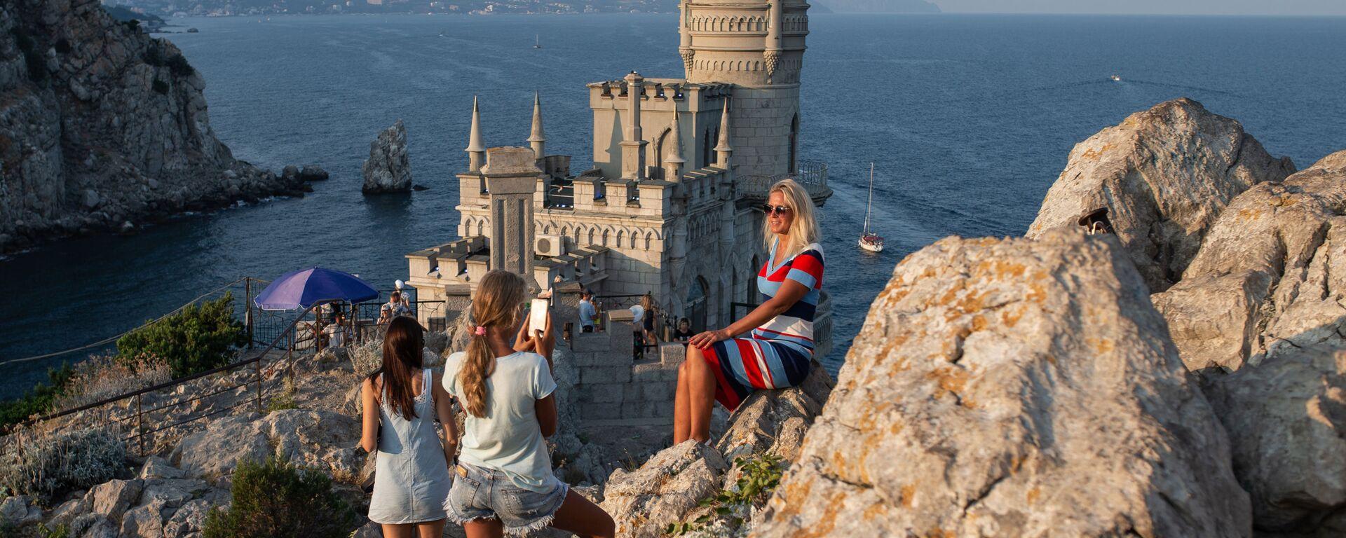 Отдыхающие фотографируются возле замка Ласточкино гнездо на береговой скале в поселке Гаспра в Крыму - Sputnik Mundo, 1920, 08.09.2021
