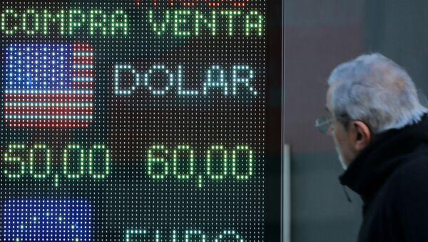 Un hombre mira la devaluación del peso argentino frente al dólar en una pantalla - Sputnik Mundo