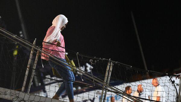Una mujer bajando del Open Arms en Lampedusa - Sputnik Mundo
