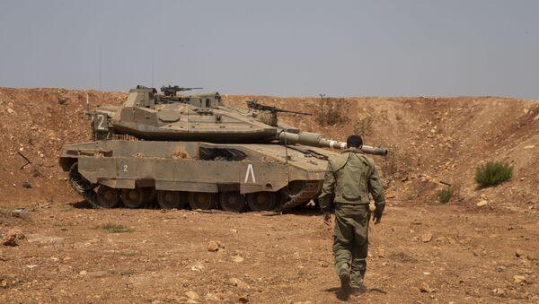 Un soldado israelí camina hacia el tanque en la frontera con Líbano - Sputnik Mundo