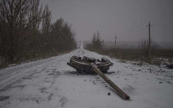 Un fragmento de una torre de tanques en la carretera, consecuencia del bombardeo del pueblo de Kominternovo, región de Donetsk (foto de la serie Zona Gris) - Sputnik Mundo