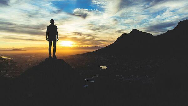 Un hombre observa la puesta del sol - Sputnik Mundo