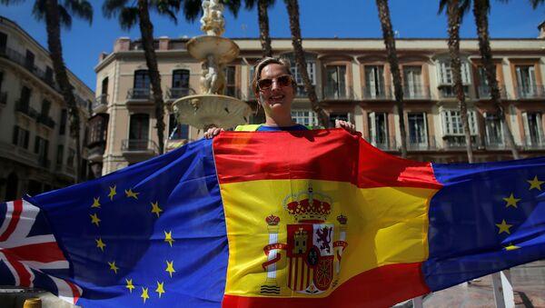 Una manifestante sostiene banderas de España, la UE y el Reino Unido durante una protesta contra el Brexit celebrada en Málaga - Sputnik Mundo
