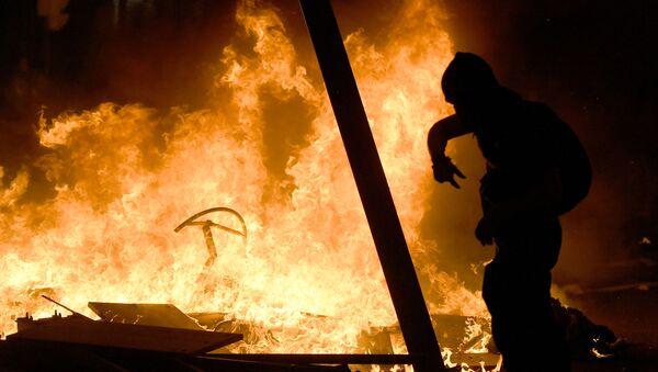 Un manifestante camina entre las barricadas en llamas durante una manifestación en Barcelona - Sputnik Mundo