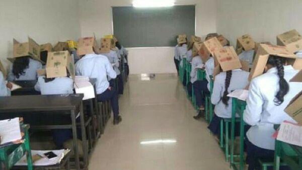 Una escuela hace a sus alumnos usar cajas en la cabeza en los exámenes - Sputnik Mundo