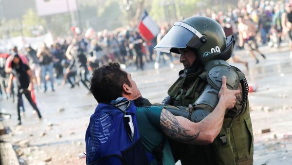 Manifestante se enfrenta a las fuerzas de seguridad de Santiago (Chile), el 24 de octubre de 2019 - Sputnik Mundo