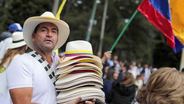 Un hombre lleva los sombreros con las banderas colombianas  - Sputnik Mundo