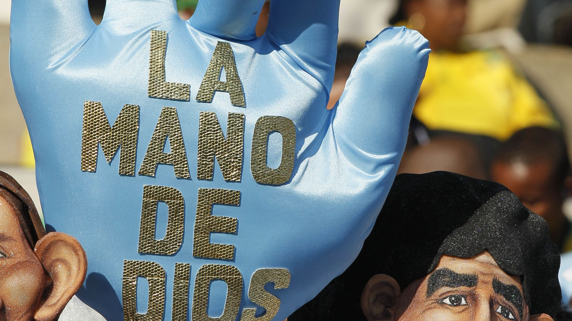 Аргентинский болельщик в маске, изображающей Марадону, и с перчаткой, на которой написано: Рука бога перед матчем Аргентина - Нигерия группового этапа ЧМ 2010 - Sputnik Mundo, 1920, 24.03.2021