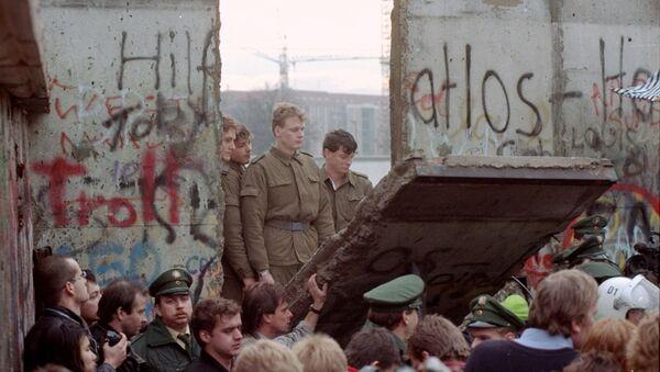 Guardias fronterizos de Alemania Oriental aparecen tras el muro de Berlín después que los manifestantes derribaron un segmento  - Sputnik Mundo